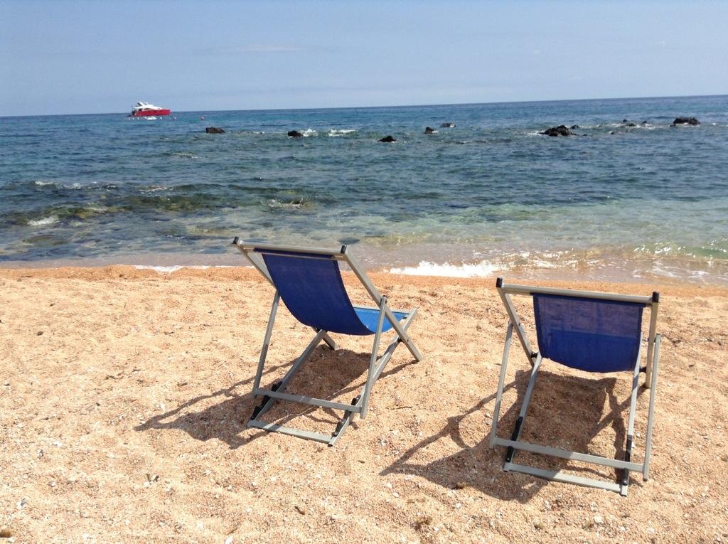 spiaggia di cala gonone con il sole sdraio