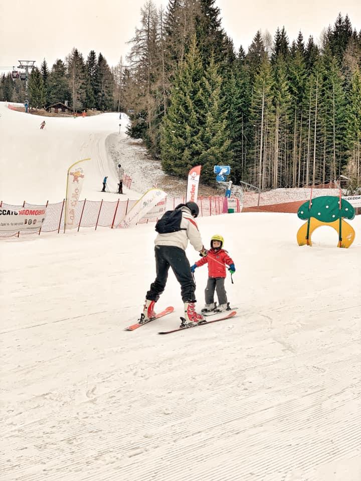 babbo che insegna a sciare a suo figlio